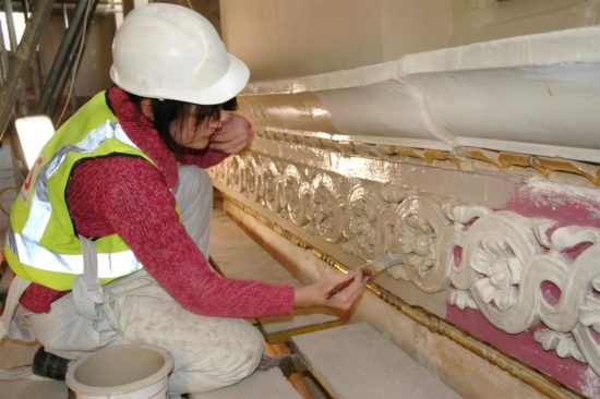A conservator restores the plasterwork back its orignal neutral colour scheme
