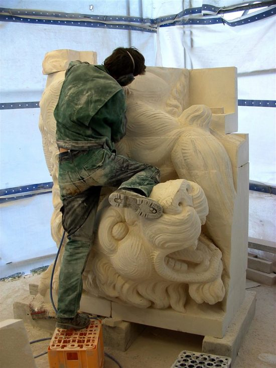 A sculptor carving the detailed patina on one of the lions