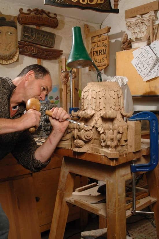 A carpenter works on a new capital for the north gallery