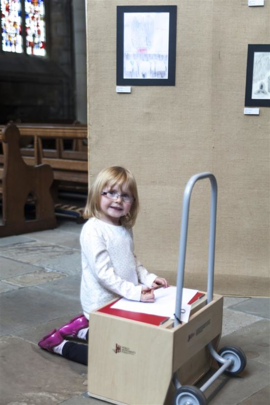 A young participant enjoying using the art materials at Durham Cathedral