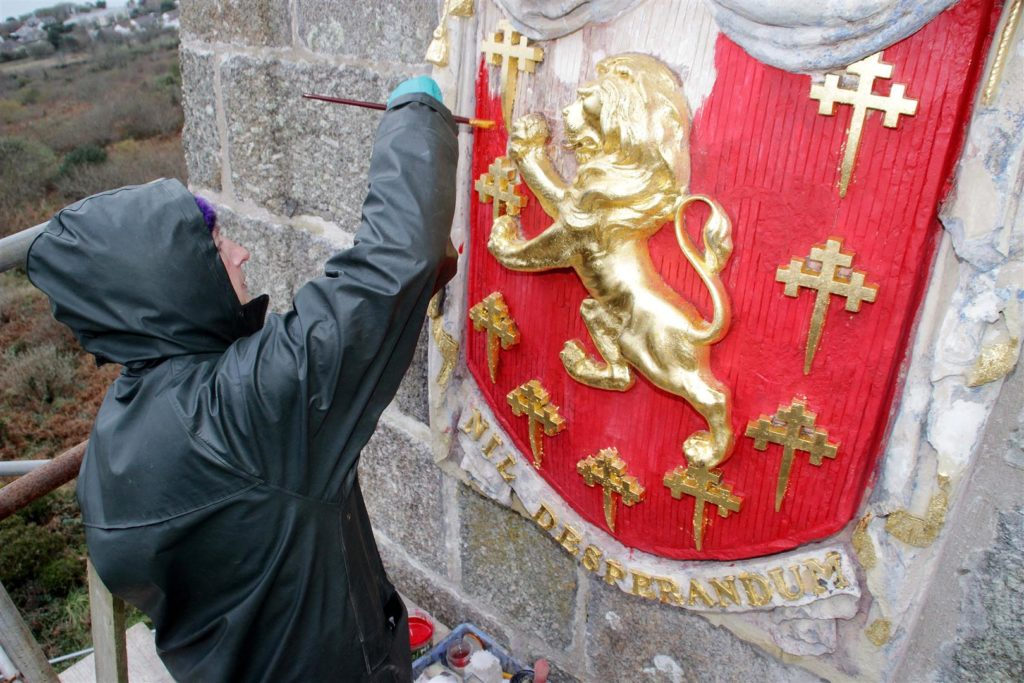 A conservator repaints the shield at Knill's Monument in St Ives