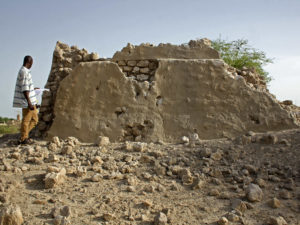 Man surveying destroyed building in Mali