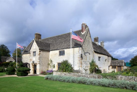 Front façade of Sulgrave Manor, with royal symbols and the arms of the family of Lawrence Washington visible on the porch
