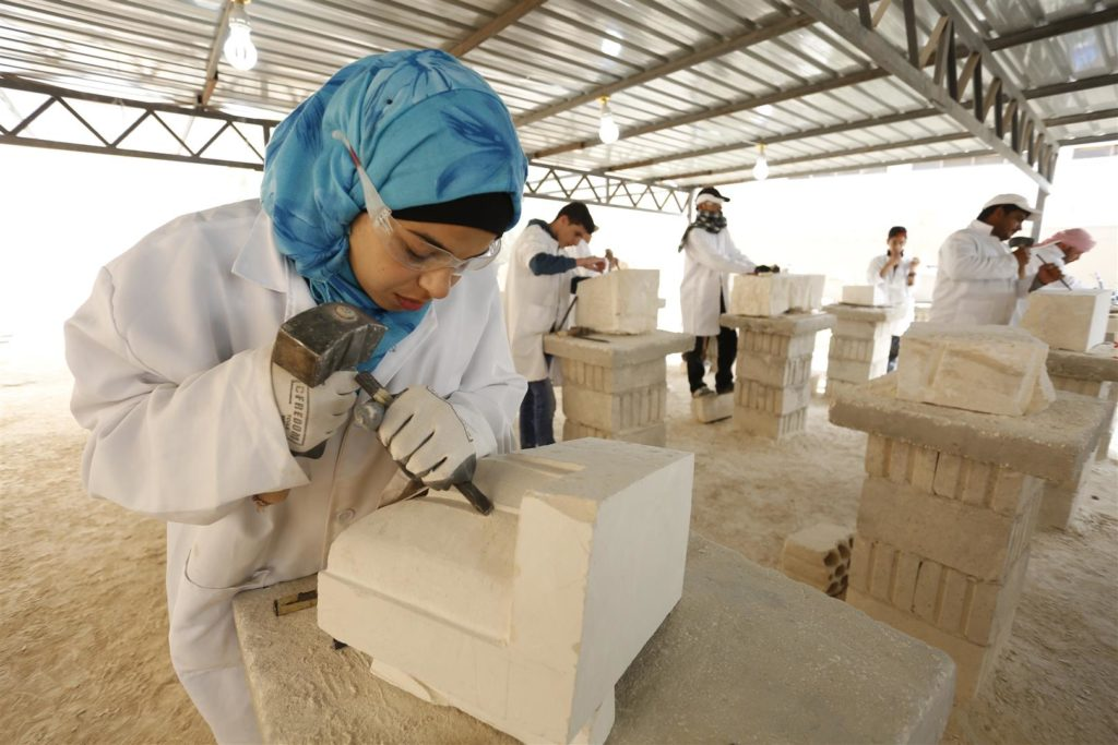 A stonemasonry Student in carves a stone at the training centre in Mafraq