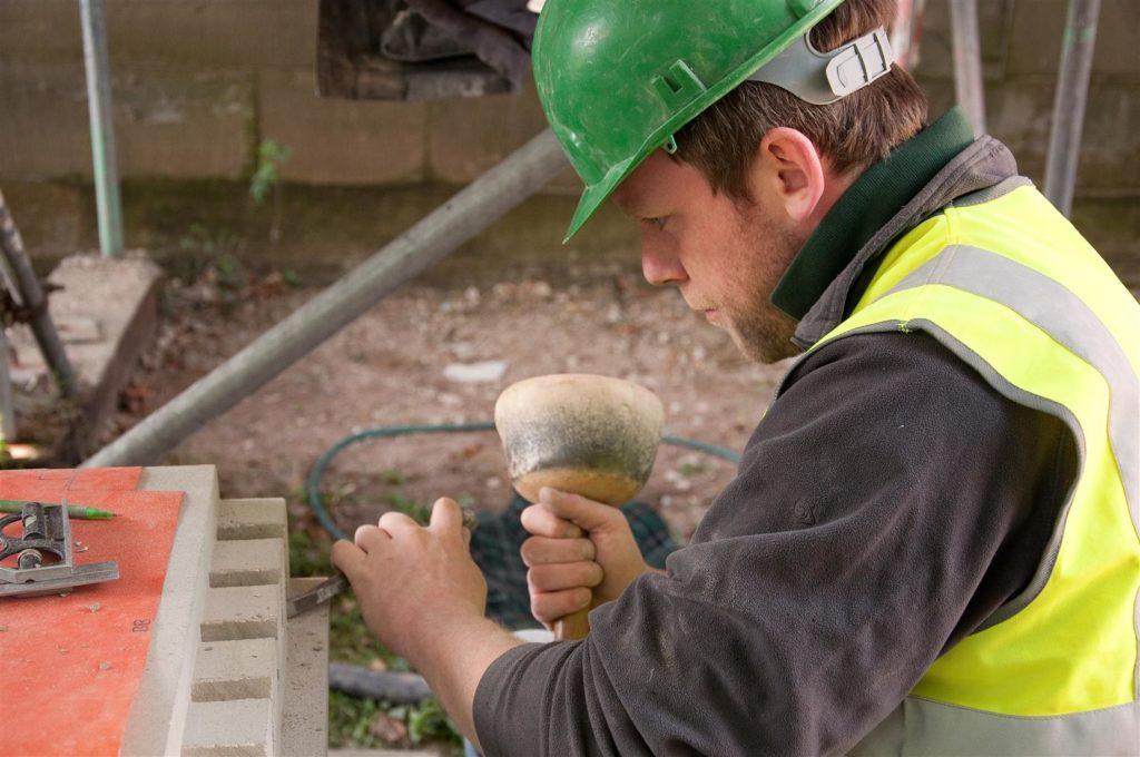A stonemason works on an exterior detail