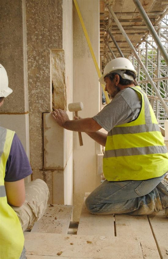 A replacement ashlar block is eased into position