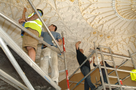 Gilding the intricate ceiling in The Long Gallery