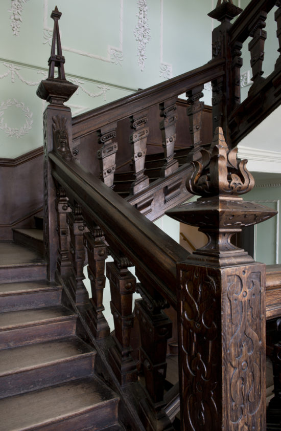 The original staircase features ornate newel posts with perforated finials and carved gargoyles at the top of each handrail