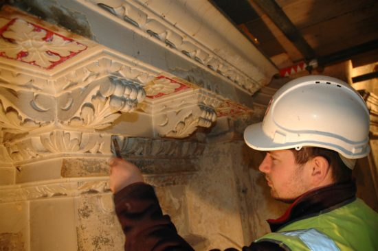 A conservator works on the dentil