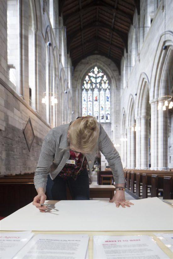 Helen Schell creating her artwork at Hexham Abbey