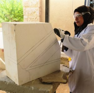 A student works on a pediment springing stone
